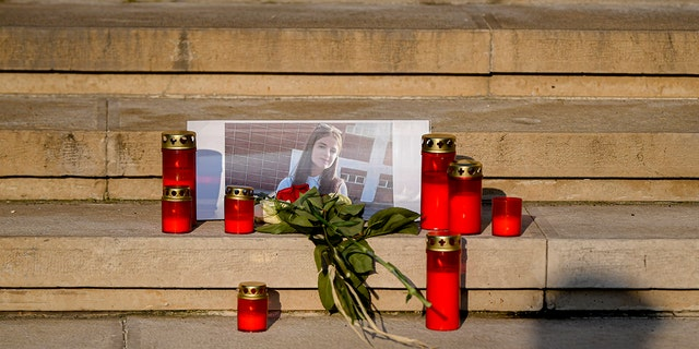 A man casts a shadow outside the Interior Ministry, in Bucharest, Romania, Friday, July 26, 2019, next to flowers and candles placed in memory of a 15 year-old girl, killed after after police took 19 hours to locate her after she was kidnapped by a man in southern Romania. (AP Photo/Andreea Alexandru)