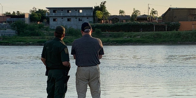 A U.S. Border Patrol official and the U.S. Drug Czar Jim Carroll look across the Rio Grande--the river that separates the U.S. and Mexico.