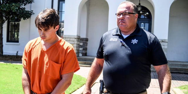 "Brandon Theesfeld, left, is led from the Lafayette County Courthouse in Oxford, Miss., Tuesday, July 23, 2019, by Maj. Alan Wilburn, after being arraigned in connection with the death of 21-year-old University of Mississippi student Alexandria ""Ally"" Kostial."