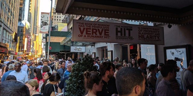 Theatergoers accumulate underneath darkened marquees on Broadway.