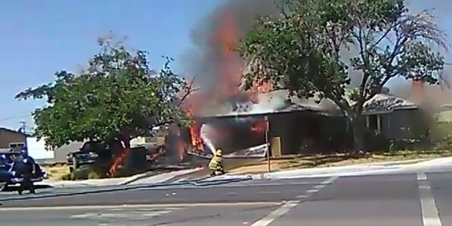In this image taken from video provided by Ben Hood, a firefighter works to extinguish a fire, Thursday, July 4, 2019, following an earthquake in Ridgecrest, Calif. (Ben Hood via AP)