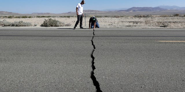 Ron Mikulaco, right, and his nephew, Brad Fernandez, examine a crack caused by an earthquake on Highway 178, Saturday, July 6, 2019, outside of Ridgecrest, Calif.