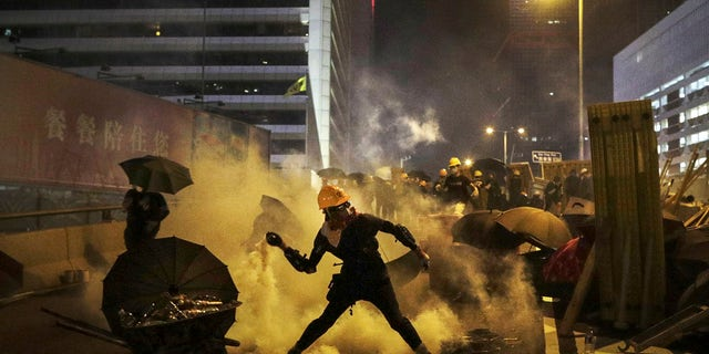 A protester throws a tear gas canister which was fired by riot police during a protest in Hong Kong, Sunday, July 28, 2019.