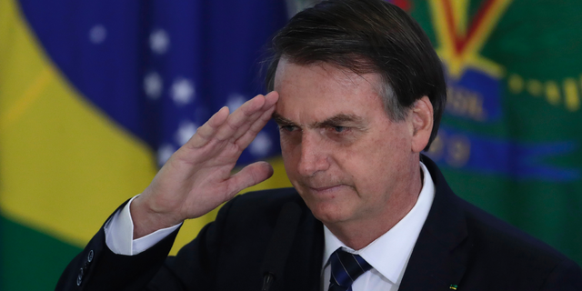 Brazil's President Jair Bolsonaro salutes during the swearing-in ceremony for the newly-named Secretary of Government Army General Luiz Eduardo Ramos at the Planalto Presidential Palace in Brasilia Brazil Thursday