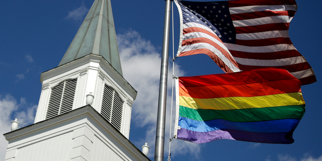 In this April 19, 2019 file photo, a gay pride rainbow flag flies along with the U.S. flag in front of the Asbury United Methodist Church in Prairie Village, Kan. A new Associated Press-NORC Center for Public Affairs Research poll shows age, education level and religious affiliation matter greatly when it comes to Americans' opinions on a prospective clergy member's sexual orientation, gender, marital status or views on issues such as same-sex marriage or abortion