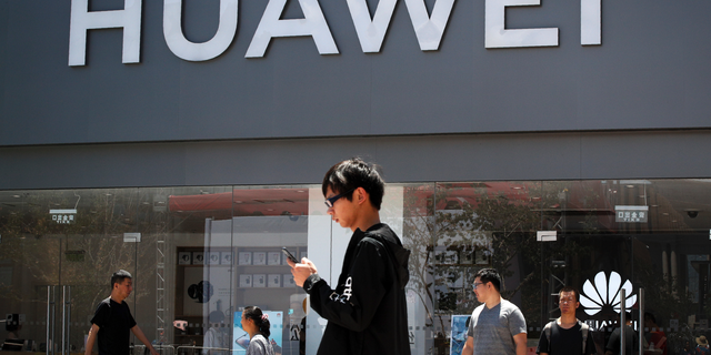 People walk past a Huawei retail store in Beijing, Sunday, June 30, 2019. (AP Photo/Andy Wong)
