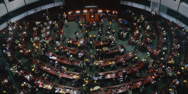 Protesters gather in the meeting hall of the Legislative Council in Hong Kong, Monday, July 1, 2019. Protesters in Hong Kong took over the legislature's main building Friday night, training down portraits of legislative leaders and spray painting pro-democracy slogans on the walls of the main chamber. (AP Photo / Kin Cheung)