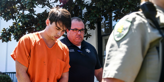 """Brandon Theesfeld, left, is led from the Lafayette County Courthouse in Oxford, Miss., Tuesday, July 23, 2019 by Maj. Alan Wilburn, after being arraigned in connection with the death of 21-year-old University of Mississippi student Alexandria """"Ally"""" Kostial."""