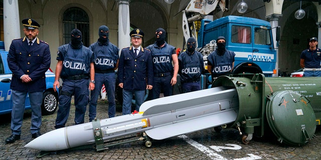 Police stand by a missile seized at an airport hangar near Pavia, northern Italy, following an investigation into Italians who took part in the Russian-backed insurgency in eastern Ukraine, in Turin, Italy.