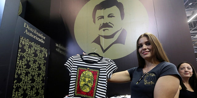 "A woman holds up a shirt from the new ""El Chapo 701"" brand, produced by the drug lord's daughter, Alejandrina Guzman."