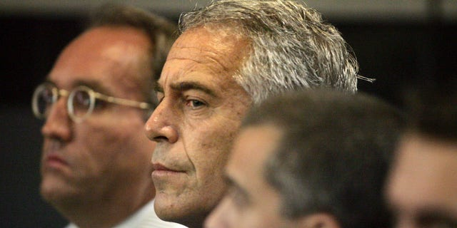 In this July 30, 2008 file photo, Jeffrey Epstein, center, is shown in custody in West Palm Beach, Fla.