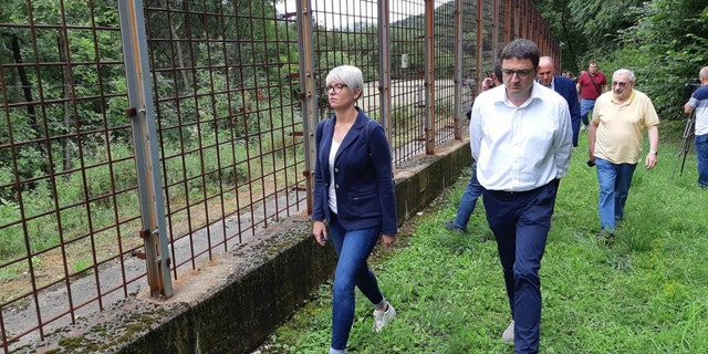 Trentino's governor Maurizio Fugatti is seen walking along the electric fence that M49 was said to climb over.