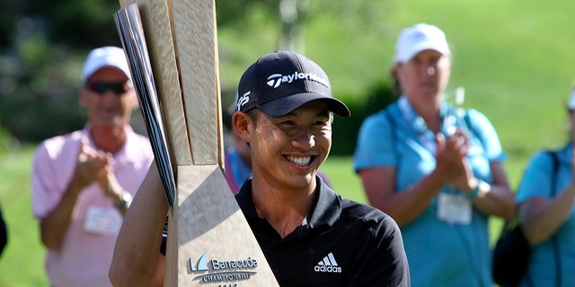 Collin Morikawa holds up his trophy for the gallery after winning the Barracuda Championship golf tournament at Montreux Golf & Country Club in Reno, Nev., Sunday, July 28, 2019. (AP Photo/ Lance Iversen)