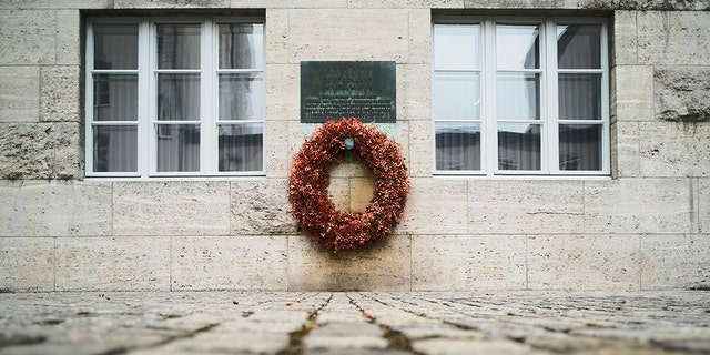 On this Friday, July 12, 2019 photo, a wreath fixed under a remembrance plaque marking the place where several leaders of the failed assassination to Adolf Hitler on July 20, 1944 were shot dead, in the courtyard of the Bendlerblock building of the German defensive ministry, in Berlin. Germany is marking the 75th anniversary of the most famous plot to kill Adolf Hitler. (AP Photo/Markus Schreiber)