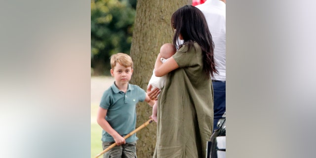Prince George of Cambridge, Meghan, Duchess of Sussex and Archie Harrison Mountbatten-Windsor attend the King Power Royal Charity Polo Match