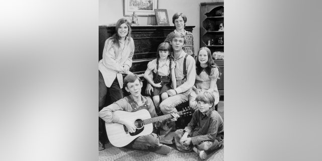 "Seated in a living room set from CBS's ""The Waltons"" television show are the children of the show, photographed in 1975, counterclockwise from bottom left, Jon Walmsley, Judy Norton, Kami Cotler, Richard Thomas, Eric Scott (standing), Mary McDonough and David Harper."