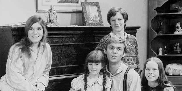 Seated in a vital room set from CBS's The Waltons radio uncover are a children of a show, photographed in 1975, counterclockwise from bottom left, Jon Walmsley, Judy Norton, Kami Cotler, Richard Thomas, Eric Scott (standing), Mary McDonough and David Harper.