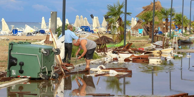 Two men search in debris after a storm at Nea Plagia village in Halkidiki region, northern Greece on Thursday, July 11, 2019.