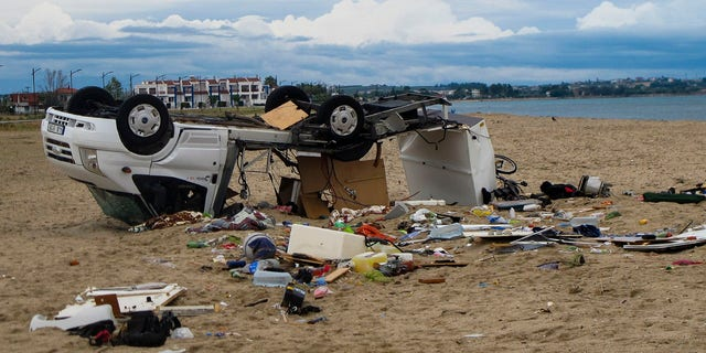 An overturned car is seen on a beach during Sozopoli encampment in Halkidiki region, northern Greece, Thursday, Jul 11, 2019.