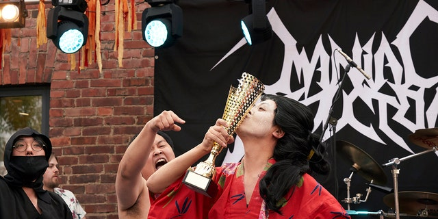 The Japanese team Giga Body Metal reacts with the trophy after being crowned Heavy Metal Knitting world champions with a show featuring crazy sumo wrestlers and team-leader Manabu Kaneko dressed in a traditional Japanese kimono knitting. (AP Photo/David Keyton)