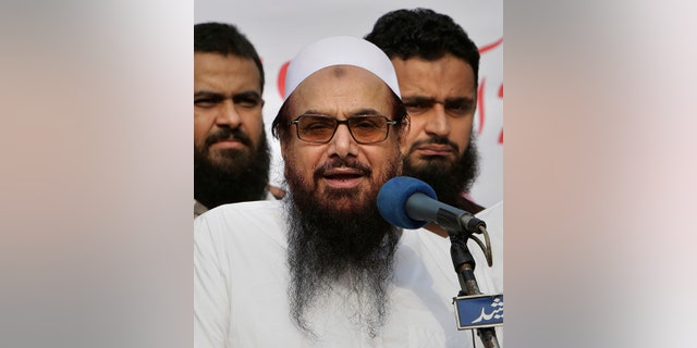 FILE - In this Friday, Oct. 26, 2018 file photo, Hafiz Saeed, founder of Pakistani religious group Jamaat-ud-Dawa addresses an anti-Indian rally in Lahore, Pakistan.  (AP Photo/K.M. Chaudary, File)