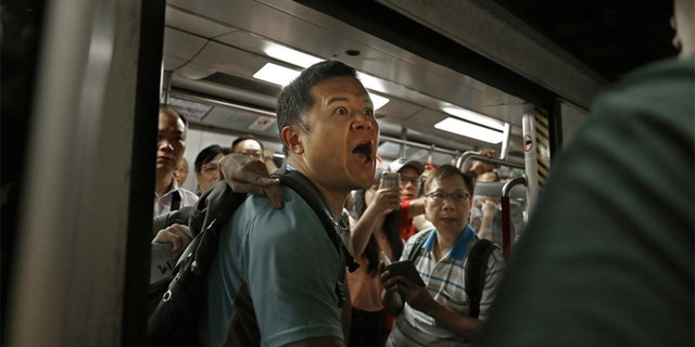 A passenger reacts after protesters blocked the train doors stopping the trains leaving at a subway platform in Hong Kong Wednesday morning. Subway train service was disrupted during morning rush hour after dozens of protesters staged what they called a disobedience movement to protest over a Sunday mob attack at a subway station. (AP Photo/Vincent Yu)