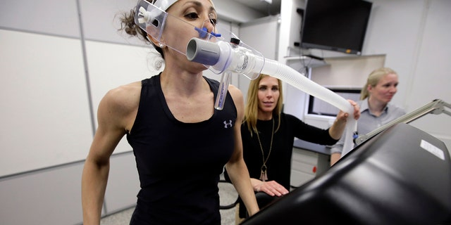Research scientist Leila Walker, left, assisted by nutritional physiologist Holly McClung, center, as they demonstrated equipment designed to evaluate fitness levels in female soldiers, not shown, this past April at the U.S. Army Combat Capabilities Development Command Soldier Center in Natick, Mass. (AP Photo/Steven Senne)