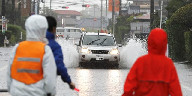 A car drives through a flooded road during heavy rain Wednesday, July 3, 2019, in Miyakonojo City,