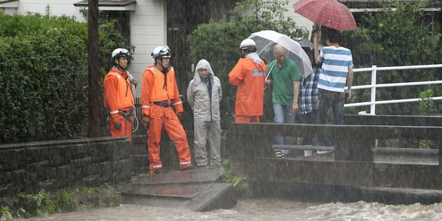 Members of the fire department monitor the water level of the Wada River in heavy rain Wednesday, July 3, 2019, in Kagoshima City, southwest Japan.