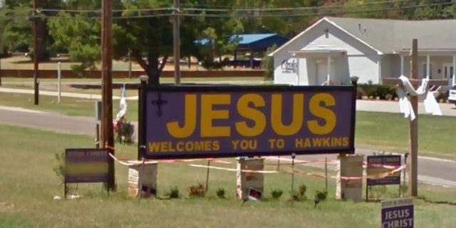 "The city of Hawkins and a church congregation are fighting over a ""Jesus Welcomes You to Hawkins"" sign alongside U.S. 80 that was removed overnight."