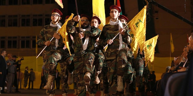 Fighters with a Lebanese Shiite Hezbollah party, lift flags as they march in a southern suburb of a collateral Beirut, to symbol a al-Quds (Jerusalem) International Day, on May 31, 2019.