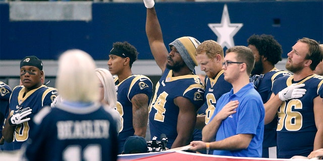 In this 2017 photo, then-Los Angeles Rams linebacker Robert Quinn (94) raising his fist during the anthem before a game against the Dallas Cowboys, in Arlington, Texas. (AP Photo/Ron Jenkins, File)
