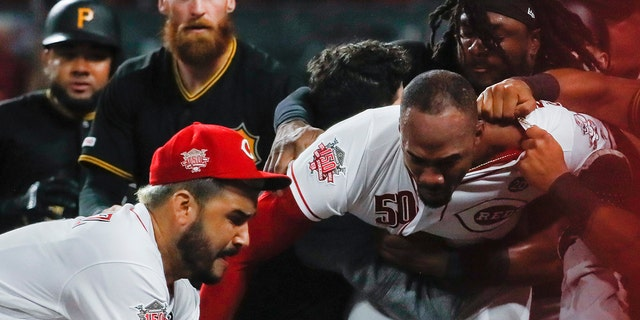 Pittsburgh Pirates' Kyle Crick (30) falls between Cincinnati Reds' Eugenio Suarez, left, and Amir Garrett (50) during a brawl in the ninth inning of a baseball game Tuesday, July 30, 2019, in Cincinnati. (AP Photo/John Minchillo)