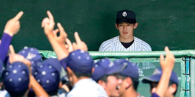 In this July 25, 2019, photo, Ofunato High School pitcher Roki Sasaki on the bench watches Hanamaki Higashi High School players celebrate their 12-2 win in their final baseball game at the Iwate Prefecture qualifier in Morioka, northern Japan. (Kyodo News via AP)