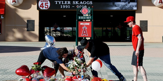 Los Angeles Angels fans prop up a memorial to give their condolences for pitcher Tyler Skaggs at Angel Stadium in Anaheim, Calif., Monday, July 1, 2019. Skaggs died at the age of 27, stunning Major League Baseball and leading to the postponement of the team's game against the Texas Rangers on Monday. (AP Photo/Alex Gallardo)
