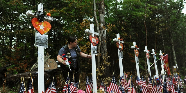 A lady views a commemorative during a site where 7 bikers roving with a Jarheads Motorcycle Club were killed in a collision final month Saturday. Thousands of motorcyclists converged during a pile-up site during a end of a 90-mile Ride for a Fallen 7 to remember a riders who were killed. (Paul Hayes/Caledonian-Record around AP)
