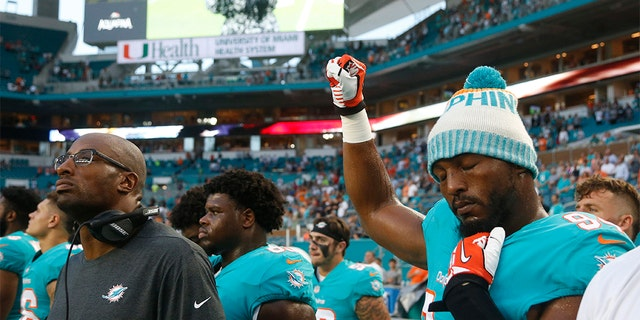 In this 2018 photo, then-Miami Dolphins defensive end Robert Quinn (94) raising his right fist during the anthem before a game against the Tampa Bay Buccaneers, in Miami Gardens, Fla. (AP Photo/Wilfredo Lee, File)