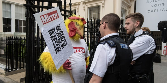 Police officers speak to a Daily Mirror campaigner dressed as a chicken outside a venue where then Chancellor of the Exchequer, Philip Hammond and Secretary of State for Exiting the European Union, David Davis, were due to speak