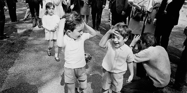 John F. Kennedy Jr. (right) with his cousins Anthony and Tina (behind), the children of Jackie's sister Lee Radziwill, in Green Park, London, on May 13, 1965. (Photo by McCabe/Express/Getty Images)
