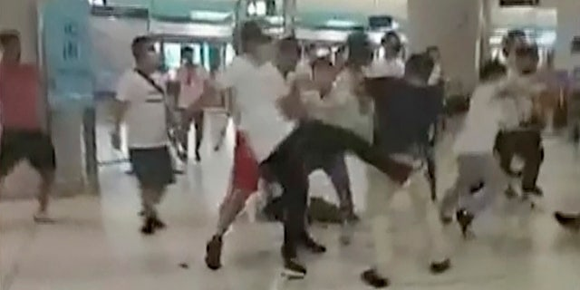 This Sunday, July 21, 2019, image taken from a video, shows confrontation between masked assailants and protesters at Yuen Long MTR train station in Hong Kong.