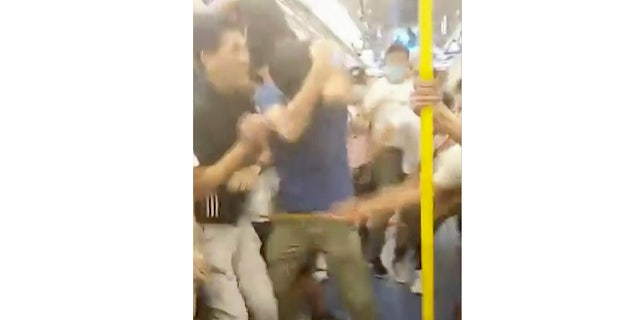 This Sunday, July 21, 2019, image made from a video, shows fighting inside a train car in Hong Kong. Protesters trying to return home were attacked inside a train station by assailants who appeared to target the pro-democracy demonstrators.