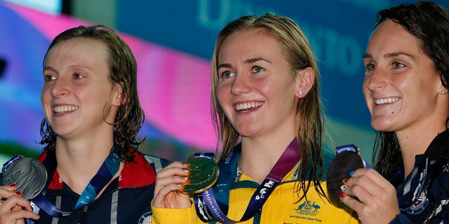 Gold medalist Australia's Ariane Titmus, centre, stands with silver medalist United States' Katie Ledecky and her compatriot and bronze medalist Leah Smith, right, following the women's 400m freestyle final at the World Swimming Championships in Gwangju, South Korea, Sunday, July 21, 2019.(AP Photo/Lee Jin-man)