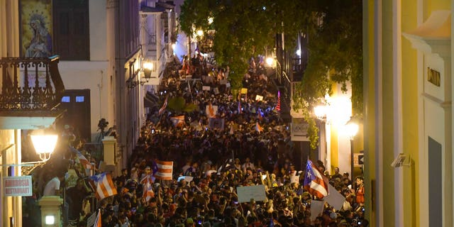 Demonstrators fill Cristo street in old San Juan, near the executive mansion to protest against governor Ricardo Rossello, in San Juan, Puerto Rico, Wednesday, July 17, 2019. Protesters are demanding Rossello step down for his involvement in a private chat in which he used profanities to describe an ex-New York City councilwoman and a federal control board overseeing the island's finance. (AP Photo/Carlos Giusti)
