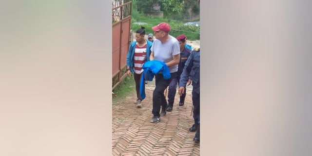 In this Monday, July 8, 2019 photo, Canadian aid worker Peter Dalglish, center wearing a red cap, is brought to appear before the Kavre District Court in Nepal. Dalglish was Monday sentenced to nine years in prison in Nepal for sexually abusing two boys who were found at his home. (AP Photo/ Janak Raj Sapkota)