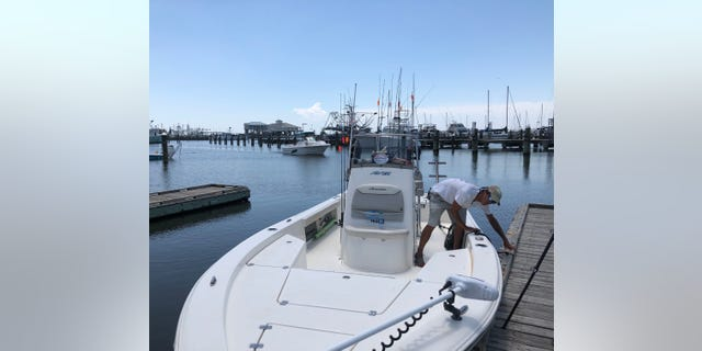 Sonny Schindler, owner and guide for Shore Thing Fishing Charters, ties his boat up to a dock. He said he's had to work harder to hold onto his customers after the emergence of the toxic algae blooms. (Fox News/ Charles Watson)