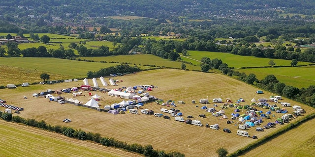 Drone cinema of a margin circuitously a Three Counties Showground uncover a red double-decker celebration train and retreat covering several double-beds.