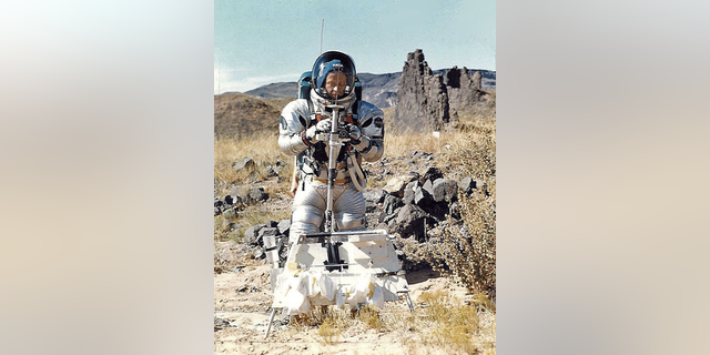 Gordon Swann in suit holding Apollo Lunar Staff prototype; tool carrier in front