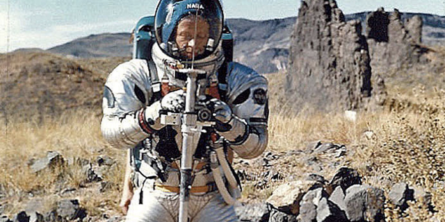 Gordon Swann in fit holding Apollo Lunar Staff prototype; apparatus conduit in front