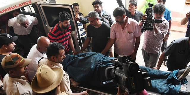 The body of missing Indian coffee tycoon V.G. Siddhartha is wheeled on a stretcher from an ambulance to a cold storage unit after local fishermen found it floating in the Netravati river in the coastal city of Mangalore in the southern state of Karnataka on July 31, 2019. (STR/AFP/Getty Images)