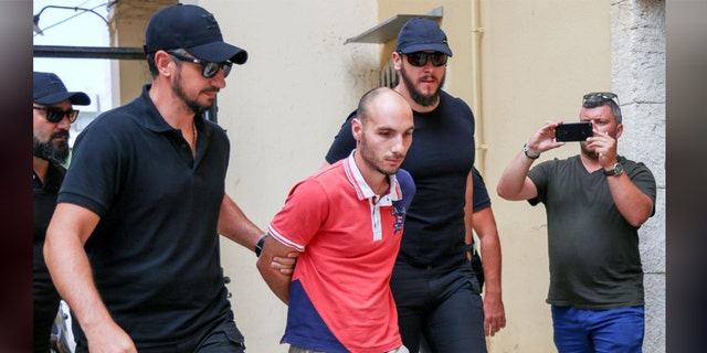 Plain-clothes police officers escort the suspect (C) for the murder of American biologist Suzanne Eaton to the prosecutor in Chania, on the island of Crete, Greece, Tuesday.